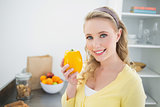 Smiling cute blonde holding a yellow pepper