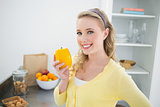 Cheerful cute blonde holding a yellow pepper
