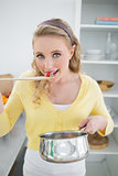 Smiling cute blonde tasting food from wooden spoon