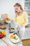 Content cute blonde phoning while preparing a meal