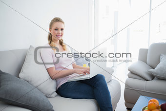 Casual smiling blonde sitting on couch using laptop