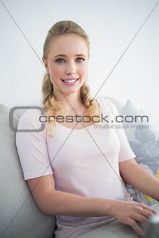 Casual cheerful blonde sitting on couch using laptop