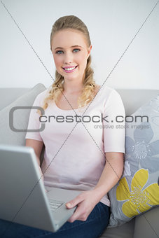 Casual smiling blonde sitting on couch holding laptop