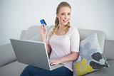 Casual happy blonde holding laptop and credit card