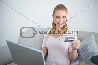Casual cheerful blonde holding laptop and credit card