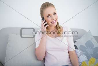 Casual smiling blonde phoning