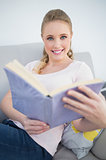 Casual cheerful blonde reading a book