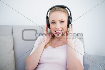 Casual cheerful blonde listening to music