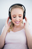 Casual smiling blonde listening to music with closed eyes