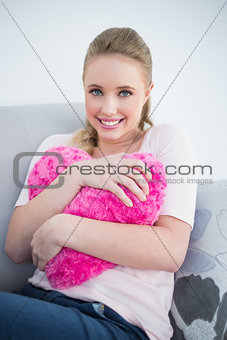 Casual cheerful blonde holding heart pillow