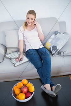 Casual smiling blonde phoning and using laptop