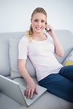 Casual cheerful blonde phoning and using laptop