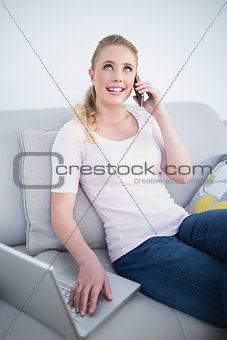 Casual happy blonde phoning and using laptop