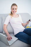 Casual cheerful blonde using smartphone and laptop