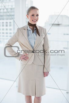 Blonde smiling businesswoman standing hand on hips