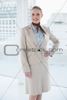 Blonde cheerful businesswoman standing hand on hips