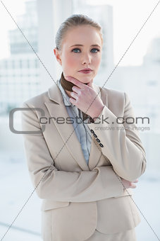 Blonde thoughtful businesswoman touching her chin