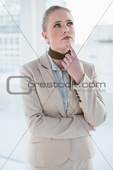 Blonde thoughtful businesswoman looking up