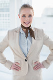 Blonde cheerful businesswoman standing hands on hips