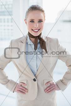 Blonde cheerful businesswoman standing hands on hips