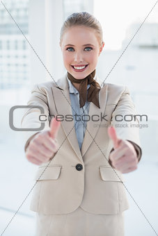 Blonde smiling businesswoman showing thumbs up