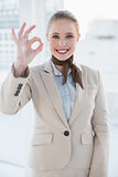 Blonde smiling businesswoman showing okay gesture