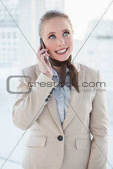 Blonde happy businesswoman phoning and looking up