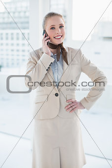 Blonde happy businesswoman phoning and standing hand on hip