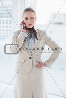 Blonde stern businesswoman phoning and standing hand on hip