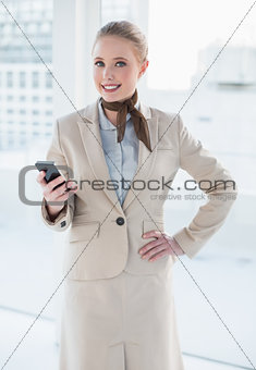 Blonde smiling businesswoman holding smartphone