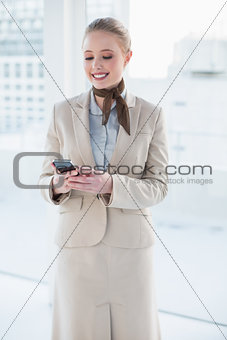 Blonde smiling businesswoman looking at smartphone