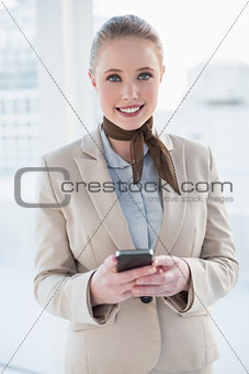 Blonde cheerful businesswoman holding smartphone