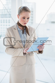 Blonde serious businesswoman looking at tablet