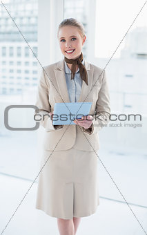 Blonde smiling businesswoman holding tablet