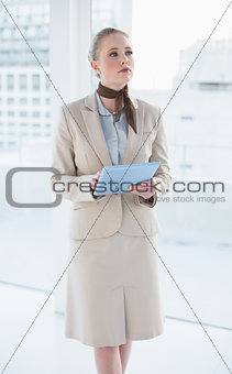 Blonde thoughtful businesswoman holding tablet