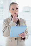 Blonde pensive businesswoman holding tablet