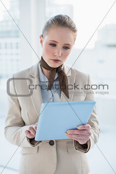 Blonde attractive businesswoman holding tablet
