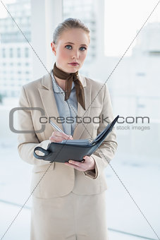 Blonde attractive businesswoman holding a diary