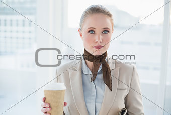 Blonde content businesswoman holding disposable cup