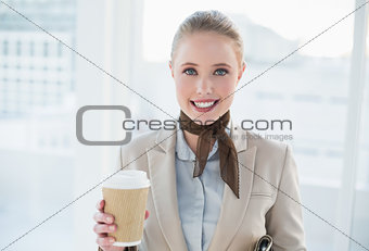 Blonde smiling businesswoman holding disposable cup