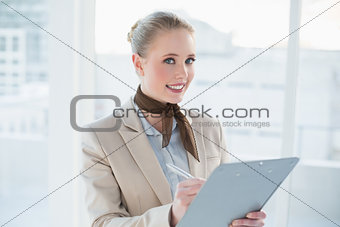 Blonde smiling businesswoman holding clipboard