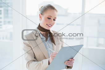 Blonde happy businesswoman holding clipboard