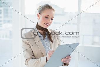 Blonde happy businesswoman holding clipboard