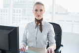 Blonde stern businesswoman sitting at desk