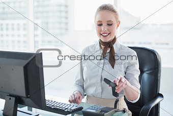 Blonde smiling businesswoman holding receiver