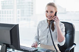 Blonde smiling businesswoman phoning at desk