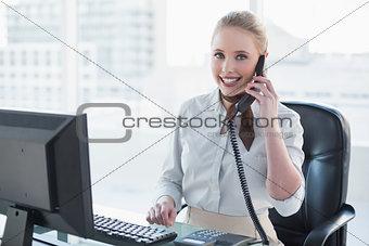 Blonde smiling businesswoman phoning at desk