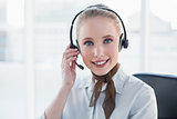 Blonde content businesswoman wearing a headset