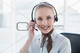 Blonde content businesswoman wearing a headset