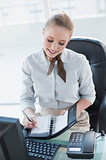 Blonde smiling businesswoman writing in diary
